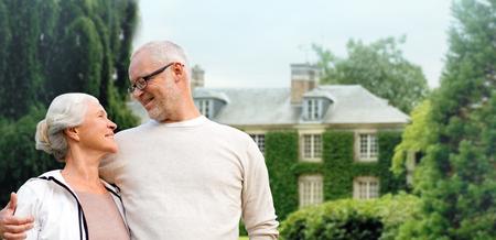 pareja en casa: la familia, la edad, el hogar, los bienes raíces y la gente concepto - feliz pareja senior abrazando sobre casa viva fondo Foto de archivo