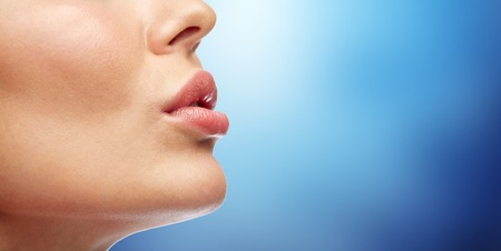 surgery concept: beauty, people, make-up and plastic surgery concept - close up of young woman lips over blue background Stock Photo