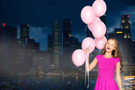 asia women: people, holidays, party, nightlife and fashion concept - happy young woman or teen girl in pink dress with helium air balloons over night singapore city background