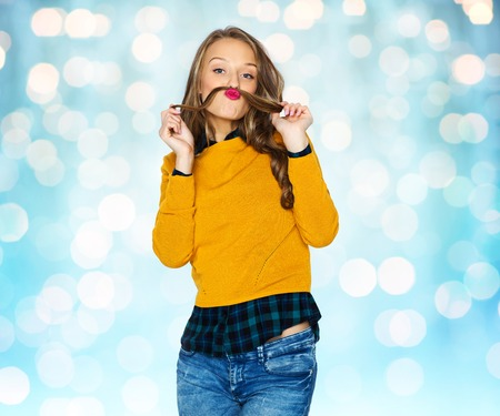 strand of hair: people, style and fashion concept - happy young woman or teen girl in casual clothes having fun making mustache of her hair strand over blue holidays lights background