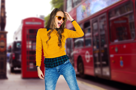 bus: people, travel, tourism, style and fashion concept - happy young woman or teen girl in casual clothes and sunglasses having fun over london city street background