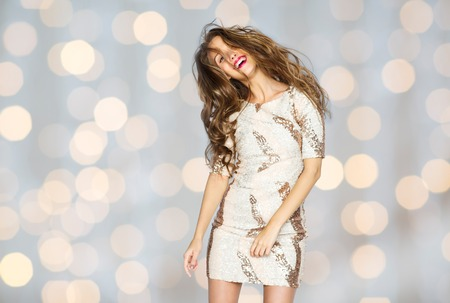 gorgeous girl: people, style, holidays, hairstyle and fashion concept - happy young woman or teen girl in fancy dress with sequins and long wavy hair dancing at party over lights background
