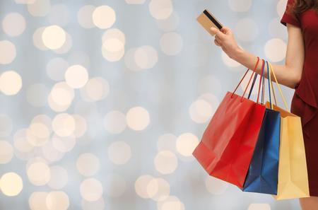 la gente, la venta y el concepto de consumo - cerca de la mujer con bolsas de la compra y la tarjeta de crédito bancaria o durante las vacaciones luces de fondo