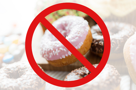 low carb diet: fast food, low carb diet, fattening and unhealthy eating concept - close up of glazed donuts behind no symbol or circle-backslash prohibition sign Stock Photo