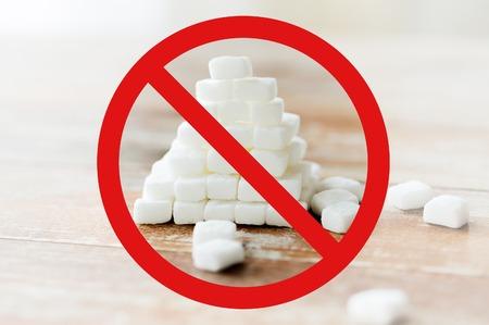 piramide alimenticia: comida, comida basura, la dieta y la alimentación poco saludable concepto - cerca de la pirámide de azúcar blanco en la mesa de madera sobre el círculo rojo-barra invertida ningún signo