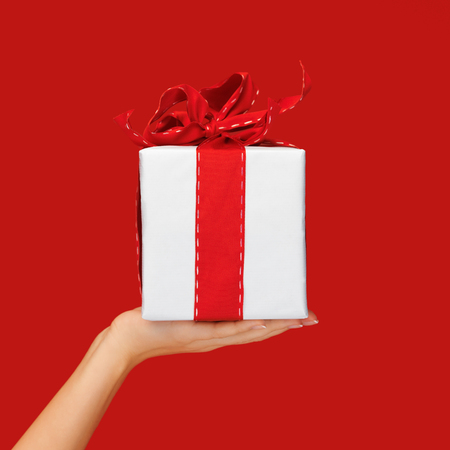 surprise box: people, holidays, present, surprise and birthday concept - close up hand holding christmas gift box over red background