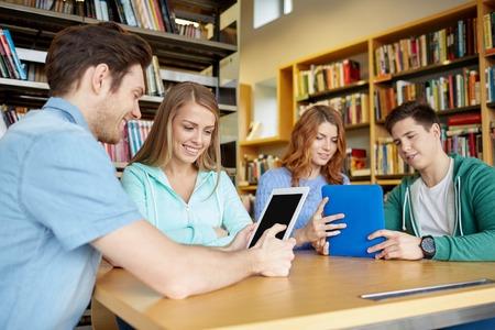 las personas, la educación, la tecnología y concepto de la escuela - estudiantes felices con la computadora Tablet PC en red en la biblioteca