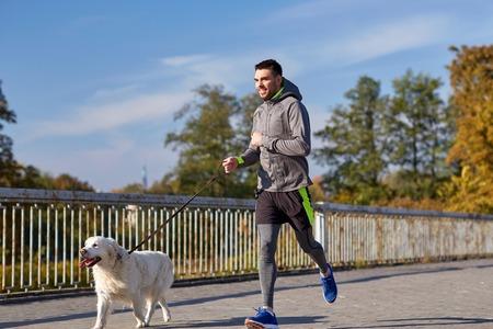 perro corriendo: fitness, deporte, personas, mascotas y el estilo de vida concepto - hombre feliz con labrador retriever perro correr al aire libre
