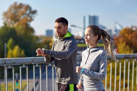 フィットネス、スポーツ、人、技術、健康的なライフ スタイル コンセプト - 都市高速道路橋の上を実行している心拍数を見るとカップルの笑顔 写真素材