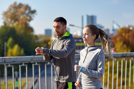 watch over: fitness, sport, people, technology and healthy lifestyle concept - smiling couple with heart-rate watch running over city highway bridge