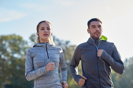 people listening: fitness, sport, people, technology and lifestyle concept - happy couple running and listening to music in earphones outdoors