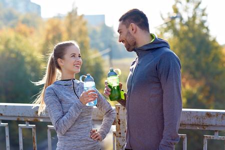 ropa deportiva: fitness, deporte, la gente y el estilo de vida concepto - sonriente pareja con botellas de agua al aire libre