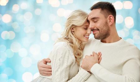 parejas enamoradas: familia, amor, invierno, días de fiesta y la gente concepto - feliz pareja durante las vacaciones las luces azules de fondo Foto de archivo