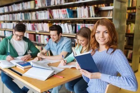 personas leyendo: las personas, el conocimiento, la educación, la literatura y el concepto de la escuela - estudiantes felices leyendo libros y que se preparan para los exámenes en la biblioteca