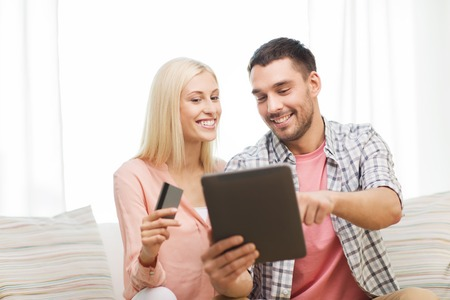 technology, people, e-money and commerce concept - smiling happy couple with tablet pc computer and credit or bank card shopping online at home