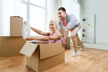 couple having fun: home, people, moving, time and real estate concept - happy couple having fun and riding in cardboard boxes with clock at new home