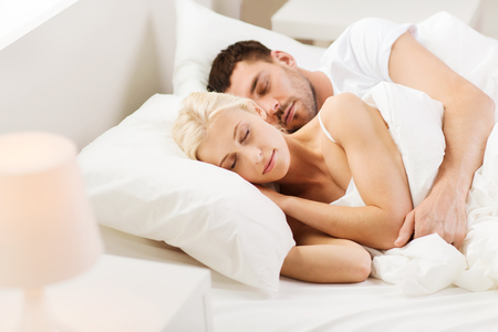 people, family, bedtime and happiness concept - happy couple sleeping and hugging in bed at home Stock Photo