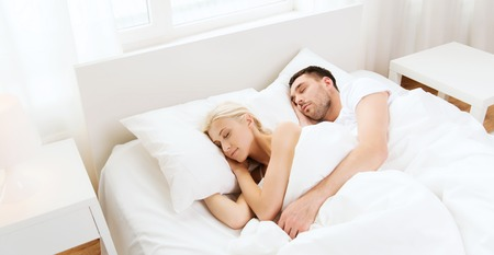 sleeping: people, rest, relationships and happiness concept - happy couple sleeping in bed at home
