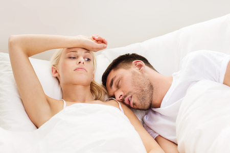 unsatisfied: people, family, bedtime and insomnia concept - unhappy woman having sleepless night with sleeping and snoring man in bed at home