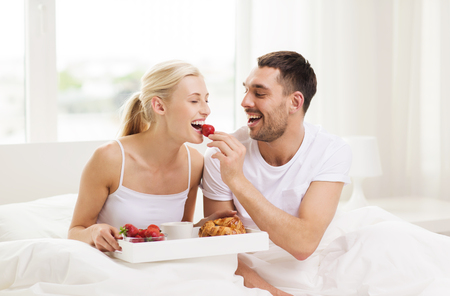 concept hotel: people, love, care and happiness concept - happy couple having breakfast in bed and eating strawberries at home