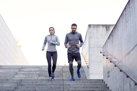 фитнес: фитнес, спорт, упражнения, люди и концепции жизни - пара идет вниз по лестнице на стадионе
