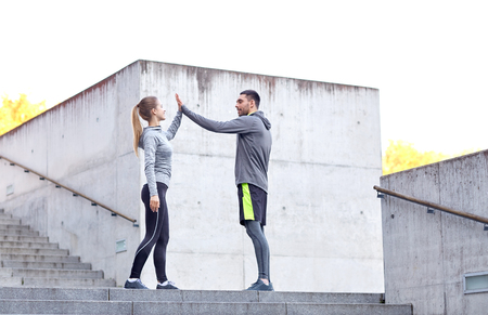 give: fitness, sport, gesture, people and success concept - happy couple giving high five outdoors