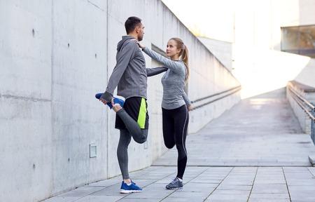 フィットネス、スポーツ、人々、ライフ スタイル コンセプト - ストレッチ足を屋外でカップルの笑顔