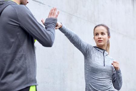 防衛: フィットネス、スポーツ、格闘技、自衛と人々 の概念 - ストライク屋外ワークアウトのパーソナル トレーナーと女性 写真素材