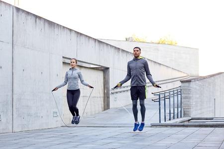 フィットネス、スポーツ、人、運動、ライフ スタイル コンセプト - 男と女の縄跳び屋外でスキップ