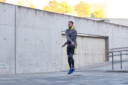 siłownia, sport, ludzie, wykonywaniu i koncepcji życia - mężczyzna omijając z skakanka na zewnątrz Zdjęcie Seryjne