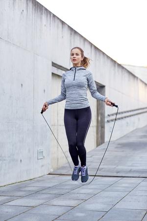 jumping: fitness, deporte, la gente, el ejercicio y el concepto de estilo de vida - mujer que salta con la cuerda de saltar al aire libre Foto de archivo
