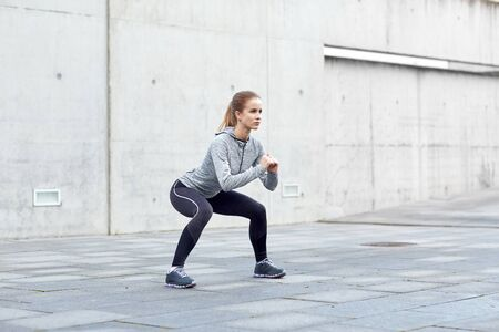 person outdoors: fitness, sport, exercising and healthy lifestyle concept - woman doing squats outdoors
