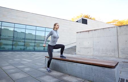 ropa deportiva: gimnasio, el deporte, la gente y el concepto de estilo de vida saludable - mujer que ejercita en banco al aire libre