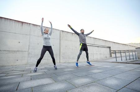 jumping: fitness, deporte, la gente, el ejercicio y el concepto de estilo de vida - hombre feliz y mujer salta al aire libre