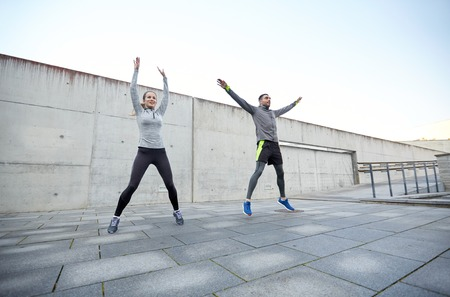 warm up exercise: fitness, sport, people, exercising and lifestyle concept - happy man and woman jumping outdoors Stock Photo