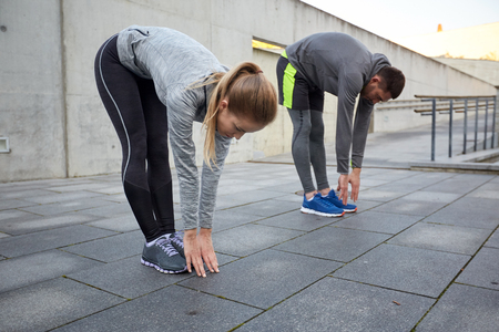bending forward: fitness, sport, exercising, people and lifestyle concept - couple stretching and bending forward on street Stock Photo