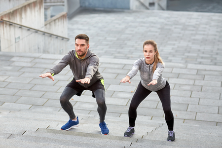 squats: fitness, sport, exercising and healthy lifestyle concept - man and woman doing squats outdoors