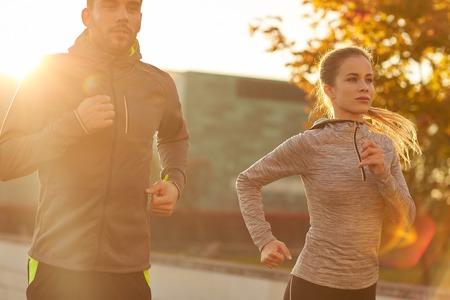 personas trotando: fitness, deporte, la gente y el estilo de vida concepto - pareja que se ejecutan al aire libre Foto de archivo