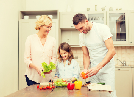 hapiness: food, family, hapiness and people concept - happy family making dinner in kitchen Stock Photo
