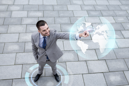 people development: global business, development, technology and people and concept - young smiling businessman pointing finger to virtual globe projection outdoors from top Stock Photo