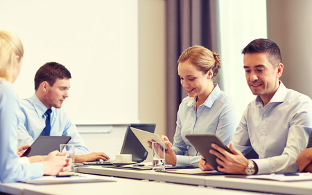 biznesu, ludzi i koncepcji technologii - uśmiechnięte działalności zespołu z komputera tablet PC spotkania w biurze