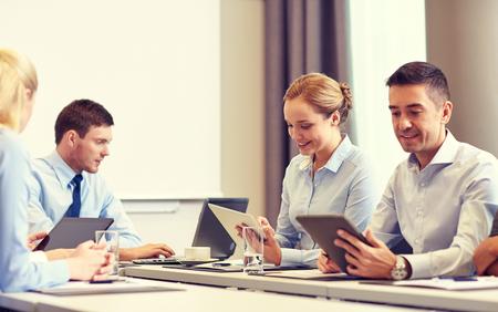 het bedrijfsleven, mensen en technologie concept - lachende business team met tablet pc computer bijeenkomst in het kantoor