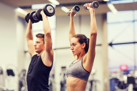 sport training: sport, fitness, lifestyle and people concept - smiling man and woman with dumbbells flexing muscles in gym