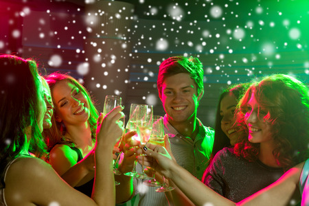 nonalcoholic: new year party, holidays, celebration, nightlife and people concept - smiling friends with glasses of non-alcoholic champagne in club and snow effect Stock Photo
