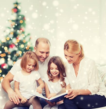 girl bonding: family, childhood, holidays and people - smiling mother, father and little girls reading book over living room and christmas tree background