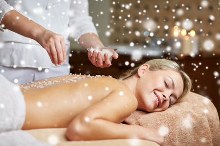 massagist: people, beauty, spa, massage and relaxation concept - close up of beautiful young woman lying with closed eyes and therapist applying sea salt to back in spa with snow effect