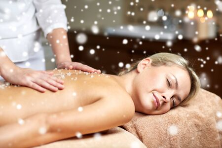 massagist: people, beauty, spa, winter and relaxation concept - close up of beautiful young woman lying with closed eyes and having salt back massage in spa with snow effect