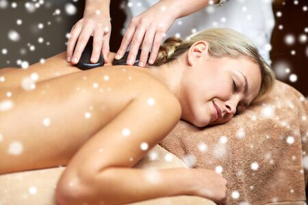massagist: people, beauty, spa, healthy lifestyle and relaxation concept - close up of beautiful young woman having hot stone back massage in spa with snow effect