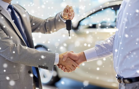 auto business, car sale, deal, gesture and people concept - close up of dealer giving key to new owner and shaking hands in auto show or salon over snow effect Archivio Fotografico