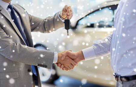 settore auto, vendita auto, affare, gesto e persone Concetto - stretta di commerciante che fornisce tasto di nuovo proprietario e stringono la mano in salone dell'auto o salone sopra effetto neve Archivio Fotografico